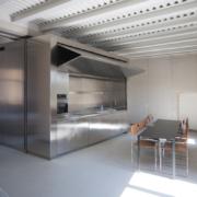 Arredo appartamento Palazzo Rhinoceros con blocco in inox che contiene la cucina e bascula motorizzata