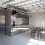 Palazzo Rhinoceros apartment furniture with stainless steel block that contains the kitchenette and has an engine-powered rocker