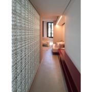 Corridoio Palazzo Rhinoceros con arredi in legno laccato rosso e parete in vetrocemento